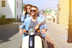Happy young couple riding scooter in town. Handsome guy and young woman travel. Adventure and vacations concept. Happy young couple riding scooter in town Royalty Free Stock Photo