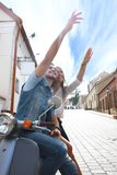 Happy young couple riding scooter in town. Handsome guy and young woman travel. Adventure and vacations concept. Stock Photos
