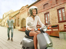 Happy young couple riding scooter in town. Handsome guy and young woman travel. Adventure and vacations concept. Royalty Free Stock Photography