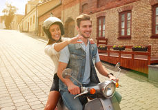 Happy young couple riding scooter in town. Handsome guy and young woman travel. Adventure and vacations concept. Stock Photo