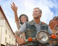 Happy young couple riding scooter in town. Handsome guy and young woman travel. Adventure and vacations concept. Royalty Free Stock Image