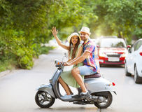 Happy young couple riding a vintage scooter in the street wearin Royalty Free Stock Photos