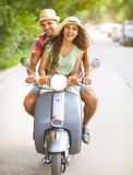 Happy young couple riding a vintage scooter in the street wearin Royalty Free Stock Images