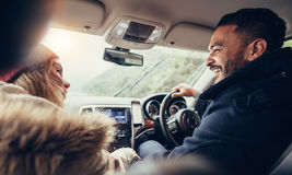Happy young couple on road trip. Man driving car with female sitting by stock photo