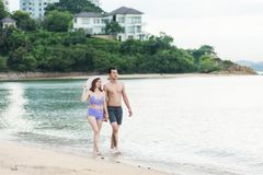 Happy young couple romantic lifestyle walking on tropical beach royalty free stock images