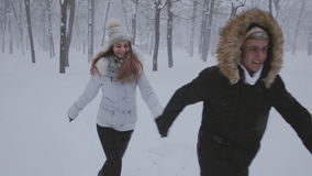 Happy young couple run in winter garden stock video footage