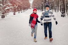 Happy, young couple runing in snowy winter park. Stock Photography