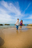 Happy young couple running on the beach Stock Photography