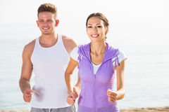 Happy young couple running on beach by sea. At daytime Royalty Free Stock Images