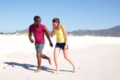 Happy young couple running on beach together. Full body portrait of happy young couple running on beach together Stock Images