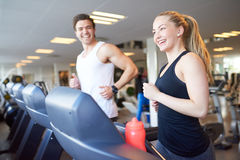 Happy Young Couple Running on Treadmill Device Royalty Free Stock Photos