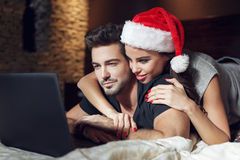 Happy young couple searching for christmas gift online Stock Photos