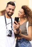 Happy young couple searching for location both on mobile phone. Couple standing in a city during there trip Stock Image