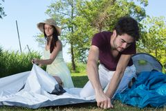 Happy young couple setting up their tent at camping site royalty free stock image