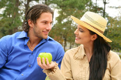 Happy Young Couple Sharing Fruits. Girl offering green apple to her boyfriend in outdoor picnic royalty free stock photography