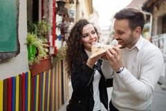 Happy young couple sharing one pizza cut Stock Photos