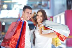 Happy young couple in shopping stock photos