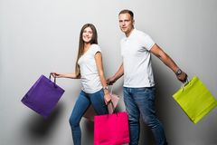 Happy young couple with shopping bags embracing and looking away isolated on white background stock photos