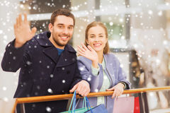 Happy young couple with shopping bags in mall. Sale, consumerism, gesture and people concept - happy young couple with shopping bags waving hands in mall with Stock Photography