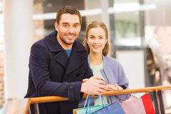 Happy young couple with shopping bags in mall Royalty Free Stock Photography