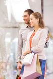 Happy young couple with shopping bags in mall Stock Images