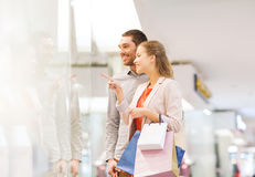 Happy young couple with shopping bags in mall. Sale, consumerism and people concept - happy young couple with shopping bags pointing finger to shop window in Stock Images