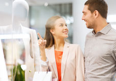 Happy young couple with shopping bags in mall Stock Photo