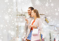 Happy young couple with shopping bags in mall. Sale, consumerism and people concept - happy young couple with shopping bags pointing finger to shop window in Royalty Free Stock Photos