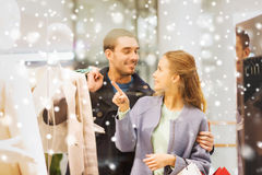 Happy young couple with shopping bags in mall. Sale, consumerism and people concept - happy young couple with shopping bags pointing finger to shop window in Royalty Free Stock Images