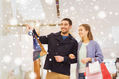 Happy young couple with shopping bags in mall. Sale, consumerism and people concept - happy young couple with shopping bags pointing finger to shop window in Stock Photo