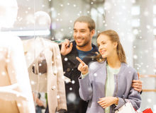Happy young couple with shopping bags in mall. Sale, consumerism and people concept - happy young couple with shopping bags pointing finger to shop window in Stock Photos
