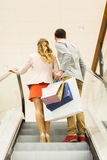 Happy young couple with shopping bags in mall. Sale, consumerism and people concept - happy young couple with shopping bags raising up by escalator and pointing Stock Photos