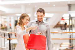 Happy young couple with shopping bags in mall. Sale, consumerism and people concept - happy young couple showing content of shopping bags in mall Royalty Free Stock Photo