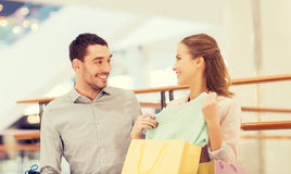 Happy young couple with shopping bags in mall Stock Photography