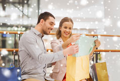 Happy young couple with shopping bags in mall. Sale, consumerism and people concept - happy young couple showing content of shopping bags in mall with snow Stock Photo