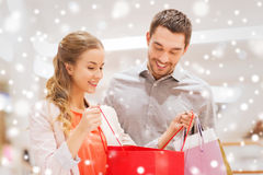 Happy young couple with shopping bags in mall. Sale, consumerism and people concept - happy young couple showing content of shopping bags in mall with snow Stock Image