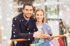 Happy young couple with shopping bags in mall. Sale, consumerism and people concept - happy young couple with shopping bags in mall with snow effect Stock Images