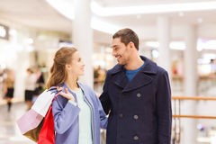 Happy young couple with shopping bags in mall Stock Photos