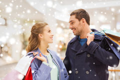 Happy young couple with shopping bags in mall. Sale, consumerism and people concept - happy young couple with shopping bags talking in mall with snow effect Royalty Free Stock Image