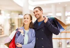 Happy young couple with shopping bags in mall. Sale, consumerism and people concept - happy young couple with shopping bags walking in mall Royalty Free Stock Photography