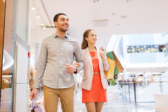 Happy young couple with shopping bags in mall. Sale, consumerism and people concept - happy young couple with shopping bags walking in mall Royalty Free Stock Photos