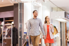 Happy young couple with shopping bags in mall Royalty Free Stock Photos