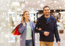 Happy young couple with shopping bags in mall. Sale, consumerism and people concept - happy young couple with shopping bags walking in mall with snow effect Royalty Free Stock Images