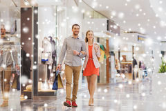 Happy young couple with shopping bags in mall. Sale, consumerism and people concept - happy young couple with shopping bags walking in mall with snow effect Stock Photo