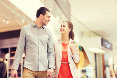 Happy young couple with shopping bags in mall Stock Image
