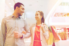 Happy young couple with shopping bags in mall. Sale, consumerism and people concept - happy young couple with shopping bags walking and talking in mall Stock Photo