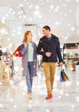 Happy young couple with shopping bags in mall. Sale, consumerism and people concept - happy young couple with shopping bags walking and talking in mall with snow Stock Photos