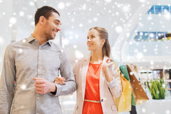 Happy young couple with shopping bags in mall. Sale, consumerism and people concept - happy young couple with shopping bags walking and talking in mall with snow Royalty Free Stock Photo