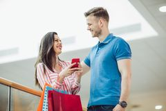 Young couple with shopping bags and smartphone talking in mall. Happy young couple with shopping bags and smartphone talking in mall Royalty Free Stock Photos