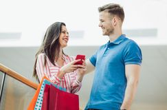 Young couple with shopping bags and smartphone talking in mall. Happy young couple with shopping bags and smartphone talking in mall Stock Images